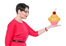 Härligt plus kakan för formatkvinnainnehav på hennes hand fotografering för bildbyråer