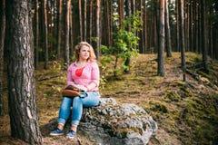 Härligt plus ungt le kvinnasammanträde för format på arkivfoton