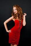 Härligt rödhårig flicka för djärvhet i en röd klänning Arkivbild