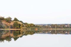 Härligt riverfrontlandskap av lugna vatten och delen av skogen Arkivbild