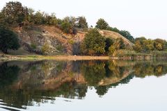 Härligt riverfrontlandskap av lugna vatten och delen av skogen Royaltyfria Bilder