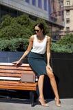 Härligt sammanträde för affärskvinna på en bänk royaltyfri fotografi
