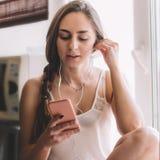 Härligt sammanträde för den unga kvinnan på fönsterbrädan lyssnar till musik fotografering för bildbyråer