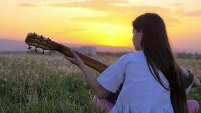 Härligt sammanträde för flicka för liten unge för solnedgång med hans baksida till kameran som spelar gitarren i ett maskrosfält  arkivfilmer