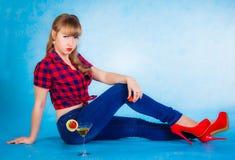 Härligt sammanträde för ung kvinna på ett golv med en coctail Arkivbilder