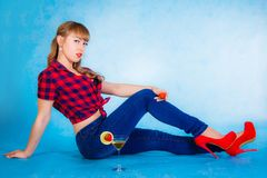 Härligt sammanträde för ung kvinna på ett golv med en coctail Arkivbild