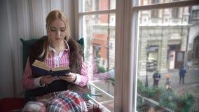 Härligt sammanträde för ung kvinna på fönsterbrädan och att läsa en bok och blickar ut fönstret stock video