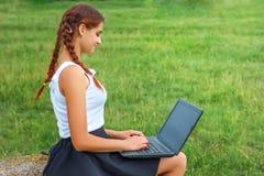 Härligt sammanträde för ung kvinna på gräs med bärbara datorn royaltyfri foto
