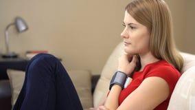 Härligt sammanträde för ung kvinna på soffan med en tonometer och att kontrollera för handled hennes blodtryck stock video