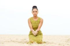 Härligt sammanträde för ung kvinna på stranden med sand som flödar från handen Royaltyfria Bilder