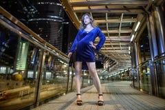 Härligt sexigt flickabrunthår, långa magra ben, modestilblått kortsluter sammetklänningen, med en svart liten påse i Hong Kong royaltyfri foto