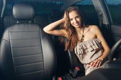 Härligt sexigt flickasammanträde bak hjulet av en bil och att le utomhus Royaltyfri Foto