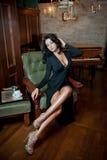 Härligt sexigt flickasammanträde på stol och att koppla av Stående av brunettkvinnan med långa ben som poserar att utmana sinnlig Arkivbild