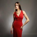 härligt sexigt kvinnabarn Skönhetflicka med den perfekta kroppen i röd klänning Arkivbild