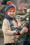 Härligt skolbarn, pojke som dekorerar julgranen på fros Arkivfoto