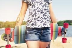 Härligt skott av den sexiga unga flickan i kortslutningar som går med färgrik longboard i soligt väder fritid Sund livsstil arkivfoto
