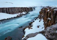 Härligt skott av en flod i en snöig stenig yttersida arkivfoto
