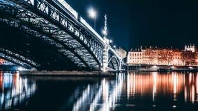 Härligt skott av en lång stålbro över en flod med ljus och reflexioner i floden på natten royaltyfri fotografi