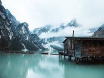 Härligt skott av ett trälitet hus vid en sjö på en pir med att förbluffa molniga och snöig berg royaltyfri foto