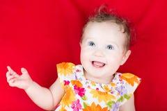 Härligt skratta behandla som ett barn flickan i en blom- klänning Fotografering för Bildbyråer