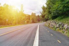 Härligt solljus på en tom landsväg royaltyfri bild