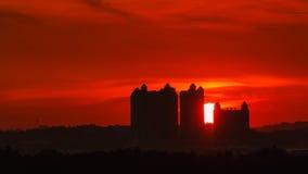 Härligt solnedgångögonblick med konturn av byggnader Arkivbild