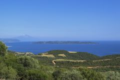 Härligt sommarhavslandskap med en sikt på den Ammouliani ön och Mount Athos Halkidiki Grekland fotografering för bildbyråer