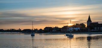 Härligt sommarsolnedgånglandskap över lågvattenhamn med hed Arkivfoto