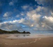 Härligt sommarsoluppgånglandskap över den gula sandiga stranden Arkivbild