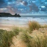 Härligt sommarsoluppgånglandskap över den gula sandiga stranden arkivfoton