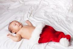 Härligt sova behandla som ett barn i Santas hatt Fotografering för Bildbyråer