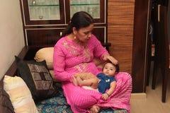 Härligt spädbarn med farmodern som ser kameran med öppna ögon fotografering för bildbyråer