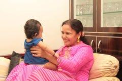 Härligt spädbarn som spelar med farmodern royaltyfria bilder