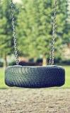 Härligt specifikt fotografi för sommarsäsong Gammalt bilgummihjul som används som en gunga för barn Lektidtema royaltyfri bild