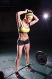 Härligt starkt, spensligt, i bra fysisk form i idrottshallen som gör övningar Iklädda korta kortslutningar och ärmlös tröja gör g Royaltyfri Foto