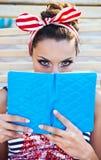 Härligt stift upp flickan som läser boken nära simbassängen Royaltyfri Foto