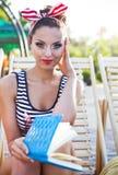 Härligt stift upp flickan som läser boken nära simbassängen Arkivfoton