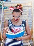 Härligt stift upp flickan som läser boken nära simbassängen Royaltyfri Bild