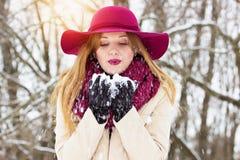 Härligt, stilfullt och ung flicka som blåser snön från henne händer Mode royaltyfri bild