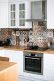 Härligt stilfullt vitt verkligt kök i skandinavisk stil med träöverkanten och spanjortegelplattor royaltyfria bilder
