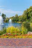 Härligt stort damm med frodiga springbrunnar som omges av högväxta gröna träd och rabatter med blommor mot blåtten Royaltyfria Foton