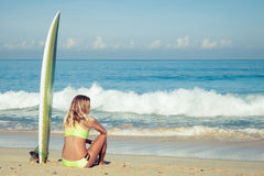 Härligt surfareflickasammanträde på stranden Royaltyfria Bilder