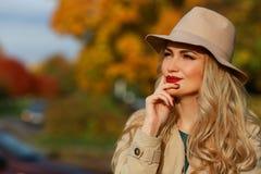 härligt tänker kvinnan Begreppshöst gul lönnträdgårdbakgrund Det lyckliga ung flickainnehav hänger lös på en vitbakgrund Arkivfoto
