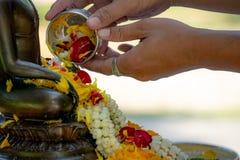 Härligt thailändskt kulturellt Hällande vatten för man som är blandat med färgglat royaltyfri foto