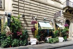 Härligt typisk romerskt kafé mycket av blommor som lokaliseras i stren royaltyfria foton