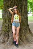 Härligt ung flickaanseende vid ett gammalt stort träd i parkera royaltyfria bilder