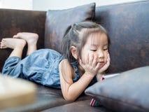 Härligt ung flickabarn som lägger ner på en soffa Arkivbild
