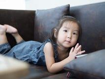 Härligt ung flickabarn som lägger ner på en soffa Arkivfoton