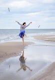Härligt ung flickaflyg med seagulls på havet Royaltyfri Foto