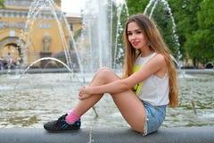Härligt ung flickasammanträde på balustradspringbrunnen på baksidan royaltyfria foton